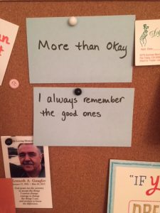 Cards pinned on a bulletin board that read 'More than Okay' and 'I always remember the good ones' also a picture of Jane Daly's brother: 'In Loving Memory Kenneth A. Gaugler Jane 27, 1952 - May 10, 2017'