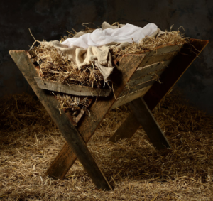 A manger filled with hay and cloths laying on top