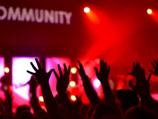 "Group of worshipers with arms raised and the word ""community"" on a screen"