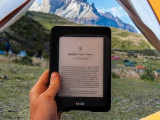 Man in a tent with mountains in the background reading on a Kindle device